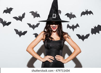 Happy gothic young woman in witch halloween costume with hat standing and smiling over white background