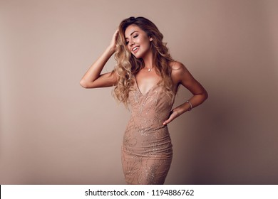 Happy graceful woman with blonde wavy hairs posing in studio. wearing elegant beige sequins  dress.