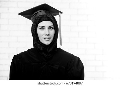 Happy graduate female muslim student poses indoors.Black and white picture.
