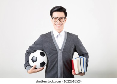 Happy graduate student holding a stack of books and a football. Studio shot on white background. Concept for Education