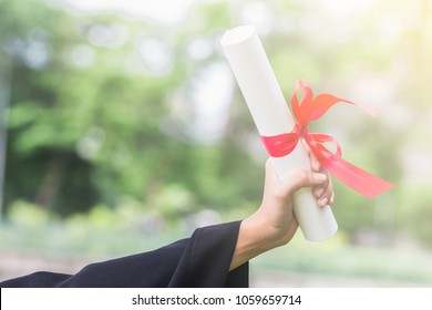 Happy graduate young Asian woman wear black gown and holding a certificated in hand, Education concept