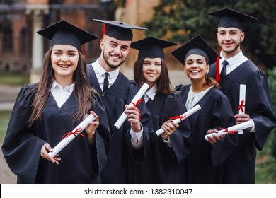 Happy graduates. Five college graduates standing in a row and smiling. Nice time!