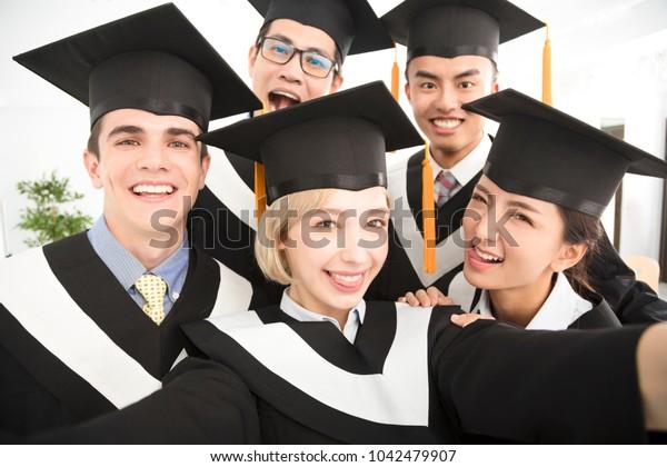 happy graduates making selfie photo in classroom