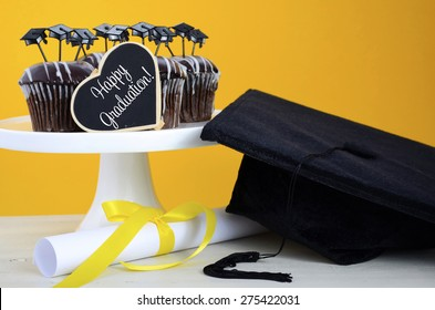 Happy Graduation Day party chocolate cupcakes with graduation cap hat topper decorations, in yellow, black and white party theme.