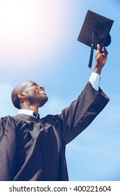 Happy graduation.. Low angle view of happy young African man in graduation gown holding his mortar board against blue sky