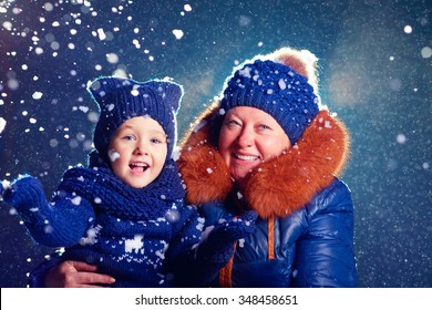 happy grandchild and grandma having fun under the snow
