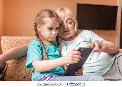 Happy grandchild teaching her grandma to use portative tablet and make selfie, online life, new normal after coronavirus pandemic, happy silver surfer an digital native generation