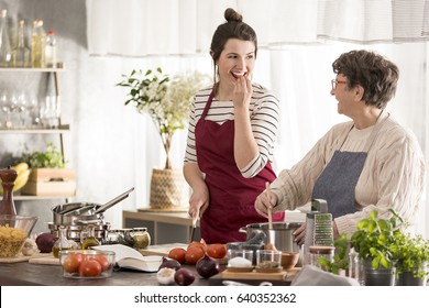 Happy granddaughter looking at her grandma while cooking