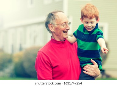 Happy grandfather carrying grandson outside