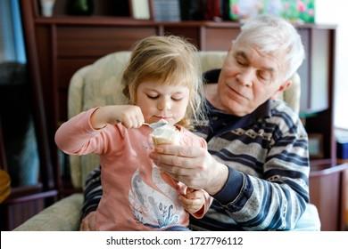 Feliz abuelo y linda nieta pequeña, adorable hijo comiendo helado juntos. La familia degustando helados dulces, la niña alimentando a un anciano.