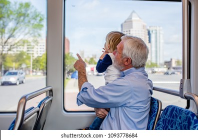 Happy Grandfather and Excited Grandson Explore the World on an Adventurous Train Ride