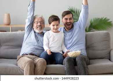 Happy grandfather, father and little son watching tv show or football match of favorite team together, eating popcorn snack, three generations of men, fans celebrating goal, sitting on couch at home