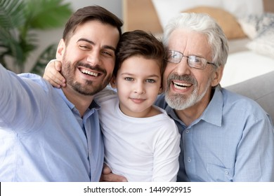 Happy grandfather, father and little son child taking selfie together, smiling granddad, dad and preschool grandchild looking at camera, family head shot portrait close up, three generations
