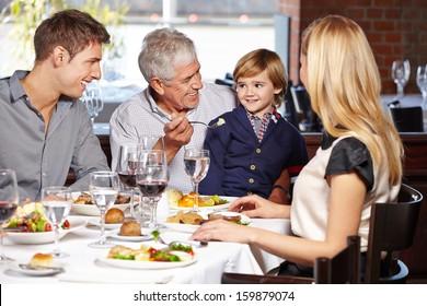 Happy grandfather feeding his grandson in a restaurant