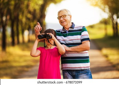 Happy grandfather and granddaughter spending time together in nature.Family moments Image is intentionally toned.