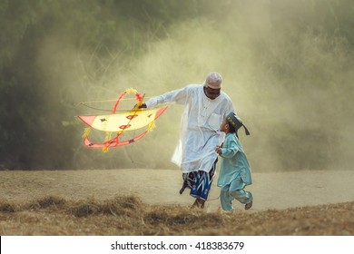 Happy grandfather and granddaughter in summer nature flying a kite