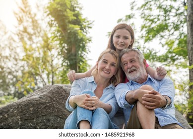 Happy grandfather grandmother and children have fun embracing and playing in park. Concept family relaxation.