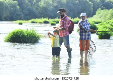 Happy grandfather and grandson are fishing on the river. Father, son and grandfather on fishing trip. Man with his son and father on river fishing with fishing rods