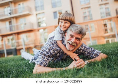 Happy grandfather and grandson lying on green grass in public park. Grandson is sitting on the grandfather's back. The grandson is hugging his grandfather