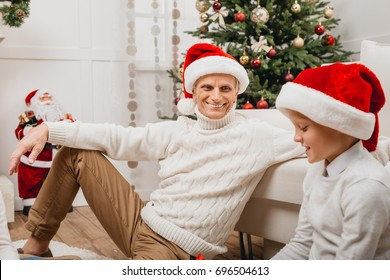 happy grandfather and grandson in santa hats sitting on floor and spending time together