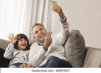 Happy grandfather and grandson taking a selfie together sitting on sofa