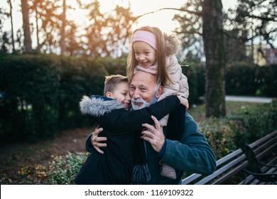 Happy grandfather having fun with his grandchildren in city park.