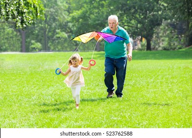 Happy Grandfather Helping Kid To Fly Kite In Park