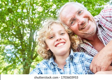 Happy grandfather and his grandson son together in the nature in summer