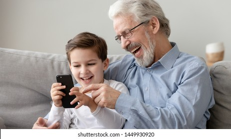 Happy grandfather and little grandson using phone, have fun together at home, laughing grandparent and cute preschool grandchild watching funny video, playing game, looking at cellphone screen