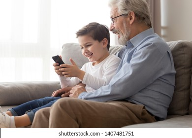 Happy grandfather and preschooler boy child relax sit on couch play game on smartphone together, excited grandparent have fun spend time with little grandson using cellphone browsing internet