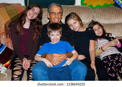 A happy grandfather sits on a mismatched couch with four of his grandchildren, three granddaughters and a grandson.