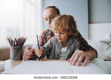 Happy grandfather and small grandson paint with colors. Children art. Leisure with grandson.