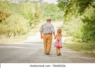happy grandfather walking with a child on his way to the park