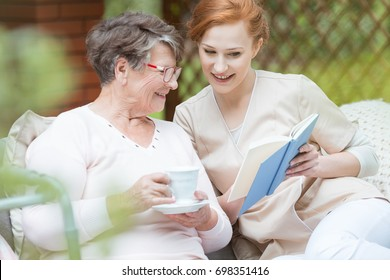 Happy grandma in glasses holding cup of coffee and watching album with photos with her nurse