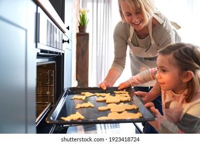 Frohe Oma mit Enkelin, die Osterkekse in den Ofen steckt