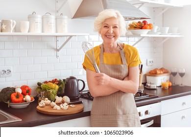 Happy grandmother in apron preparing breakfast. Morning time