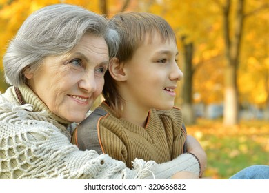 Happy grandmother with boy resting in the autumn park