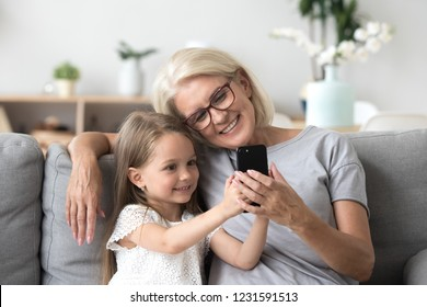 Happy grandmother and cute granddaughter using cellphone together, smiling older grandma and child girl having fun taking selfie on phone, cheerful granny with little kid play making photo on mobile