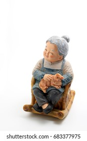 Happy grandmother doll sitting on wooden rocking chair and her cat in hand with old chinese uniform isolated on white background.