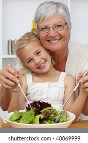 Happy grandmother eating a salad with granddaughter in the kitchen
