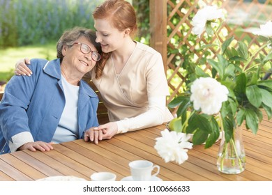 Happy grandmother enjoying time with friendly nurse on the terrace of sanatorium