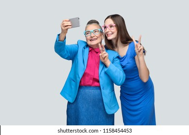 happy grandmother with granddaughter in blue dress or suit toothy smiling, standing, posing and making selfie and peace sign. Relations in the family. indoor, studio shot, isolated on gray background
