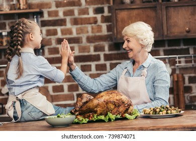 happy grandmother and granddaughter giving high five on thanksgiving after successful turkey cooking
