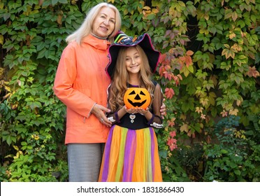 Happy grandmother and granddaughter in Halloween witch costume. Little girl and mature woman together.