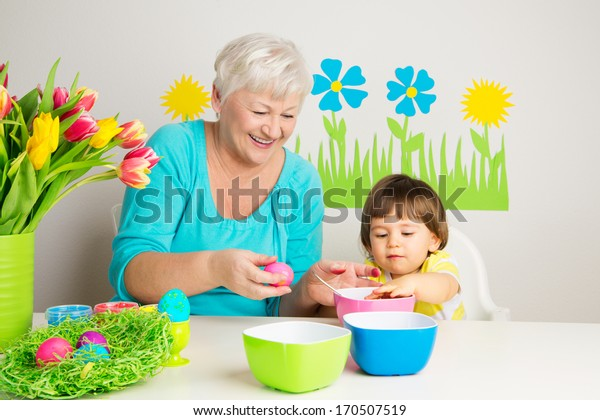 Happy grandmother and grandson color eggs for Easter at home.