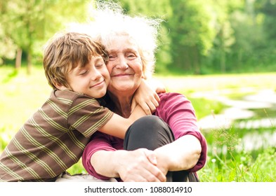 Happy grandmother with grandson together. Grandson hugs his beloved grandmother