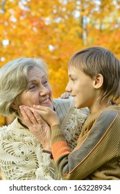 Happy grandmother with her boy resting in the autumn park