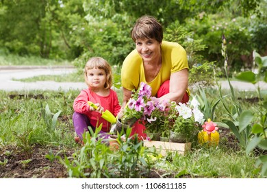 Happy grandmother with her child granddaughter working in the garden.
