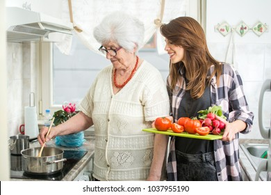 Happy grandmother and her granddaughter cooking together at kitchen.