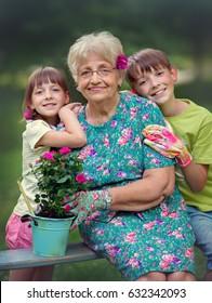 Happy Grandmother with her granddaughter working in the garden.